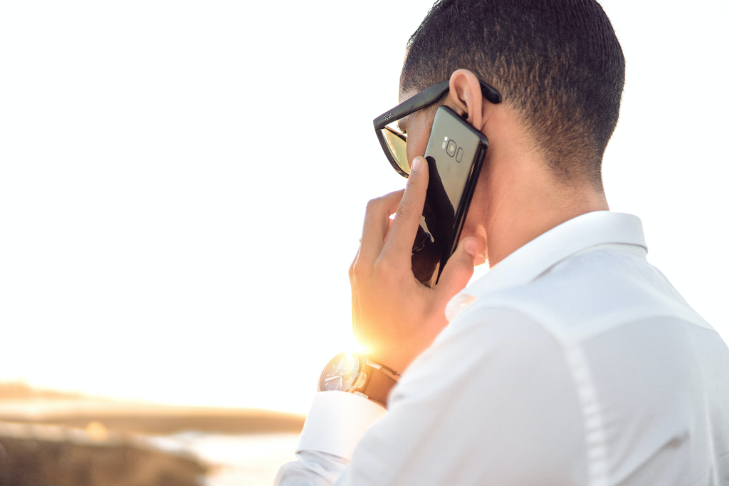 White man wearing a white shirt and black glasses holding a black smartphone to his ear. He is looking away from the camera.