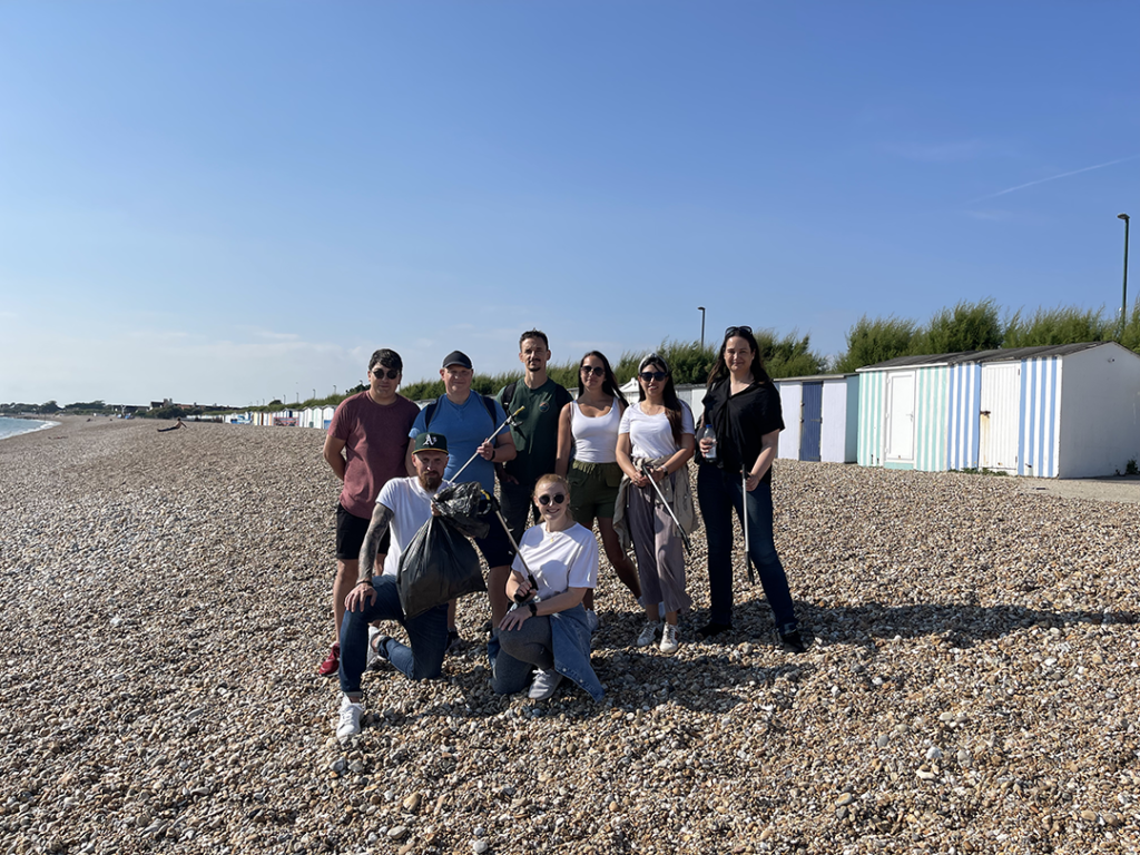 9 people stood on pebble beach in front of blue and white beach huts on a sunny day. They are all stood with a black bin bag and litter pickers in their hand.