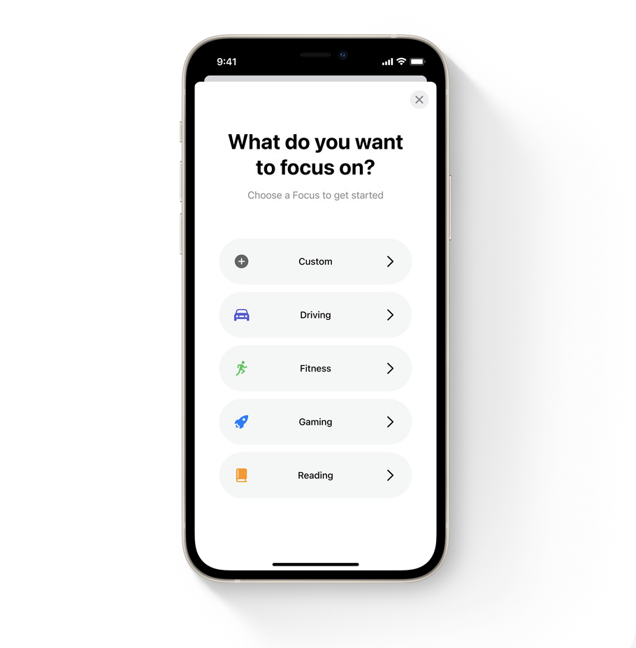 """A Black iPhone 12 showing options for the new Focus feature. The page title says """"What do you want to focus on?"""" with a subheading of """"Choose a Focus to get started"""". Below that there are 5 different focus options which are: Custom, Driving, Fitness,  Gaming and Reading."""