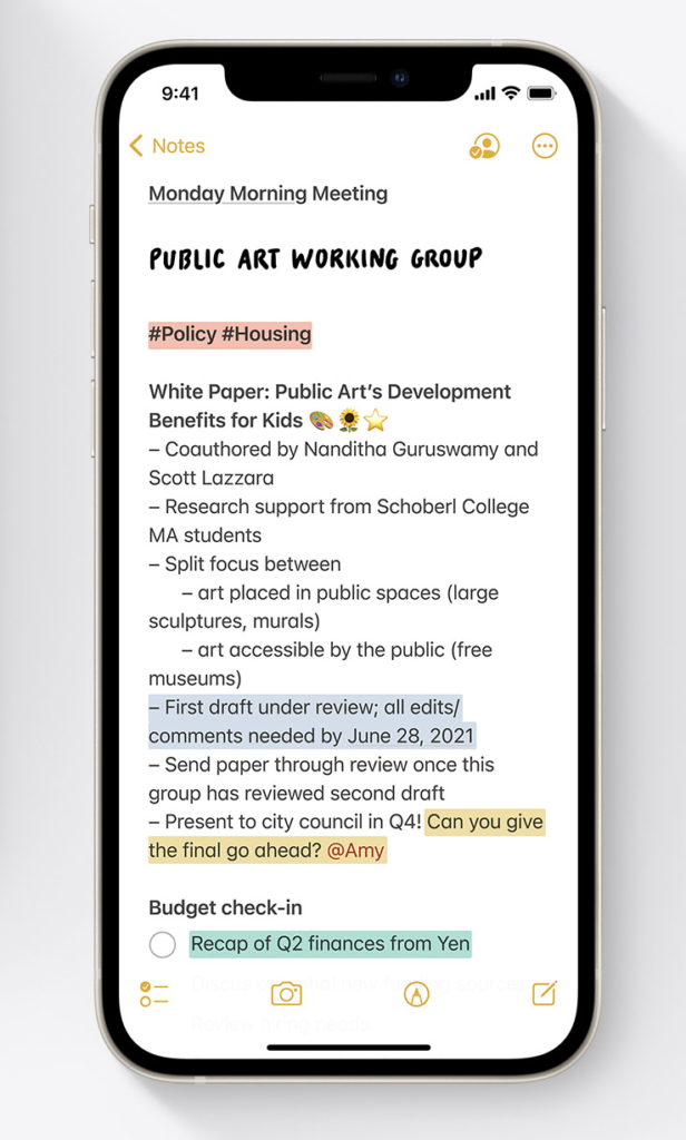 """A black iPhone 12 with the notes app open. The note says """"Monday Morning Meeting. Public Art Networking Group"""" with #Policy #Housing highlighted in red."""